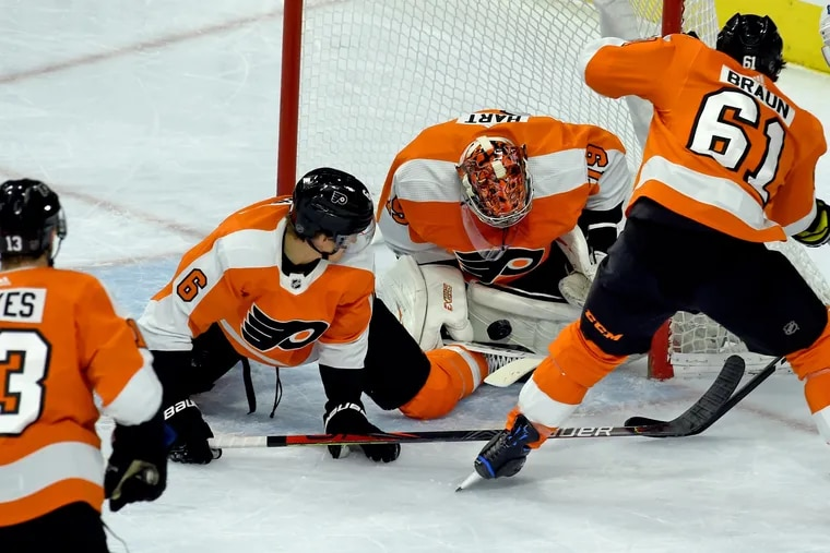 Flyers goalie Carter Hart, getting defensive help from Travis Sanheim (left) and Justin Braun (right), makes a save against Toronto.