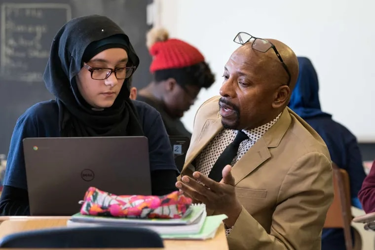 Tasneem Motan, left, and teacher Zahmu Sankofa, right, a middle-school teacher in Port Richmond, Sankofa is a singer and songwriter, he uses his background as an entertainer to keep students engaged, at James Martin MS, in Philadelphia, March 23, 2018. JESSICA GRIFFIN / Staff Photographer