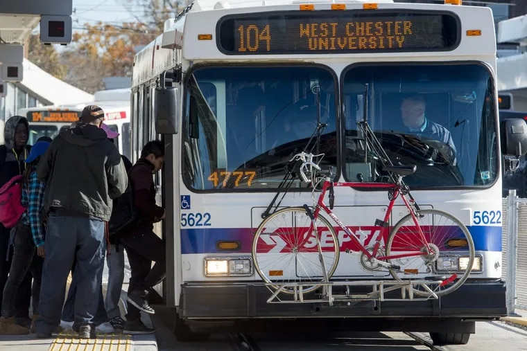 Commuters load a bus for the West Chester University at the 69th Street terminal.