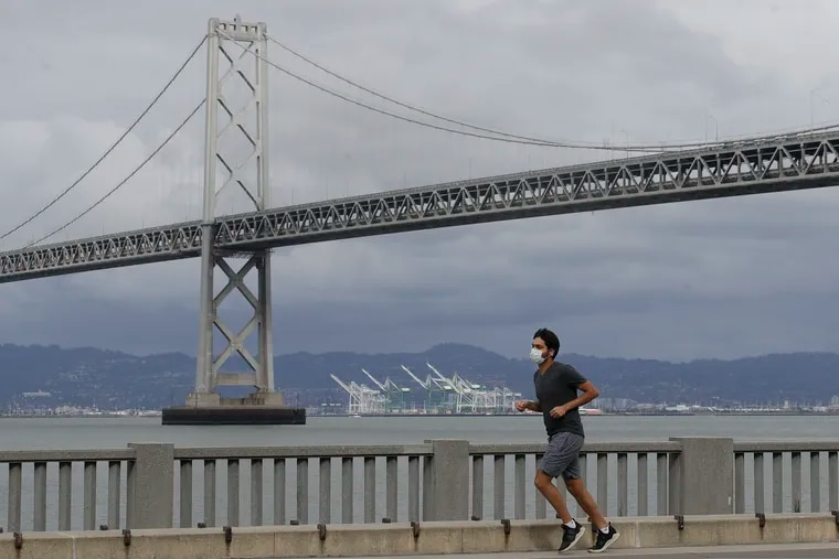 A man wears a mask to protect himself from the coronavirus while running in front of the San Francisco-Oakland Bay Bridge. San Francisco leaders say they anticipate a budget shortfall as high as $1.7 billion over the next two fiscal years.