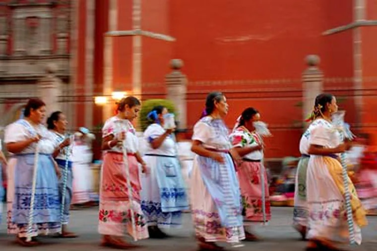 Local women, in embroidered dresses and aprons and carrying baskets of flowers, celebrate a religious holiday by the Church of San Francisco in Queretaro, Mexico. (Christopher Reynolds / Los Angeles Times)