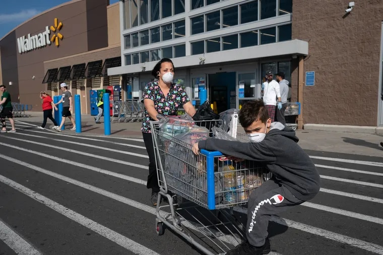 Jessica Torres Terreforte, a certified nursing assistant, and her son Daniel Terreforte, in the parking lot of Walmart at the Philadelphia Mills Shopping Center on March 20, 2020. Ms. Terreforte wears a mask and gloves, and carries hand sanitizer at the hospital where she works and in public to keep from contracting the coronavirus.