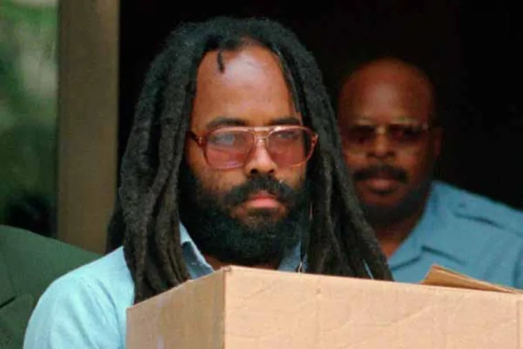 In this July 12, 1995 file photo, convicted police killer and death-row activist Mumia Abu-Jamal leaves Philadelphia's City Hall after a hearing. A day after Abu-Jamal addressed graduates of a Vermont college, a House committee advanced a bill to give the family of the police officer he was convicted of killing a way to shut him up. (AP Photo/Chris Gardner, File)