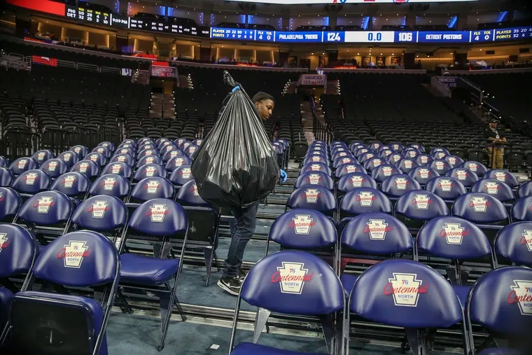 Tasha Jacobs cleans the empty seats at the Wells Fargo Center after Wednesday's Sixers-Pistons game, The NBA postponed the season shortly after the game.