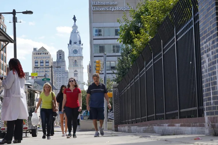 Pedestrians walk north down Broad Street on the sidewalk past Hahnemann University Hospital located at Broad and Vine Streets in Center City in Philadelphia on August 29, 2019.