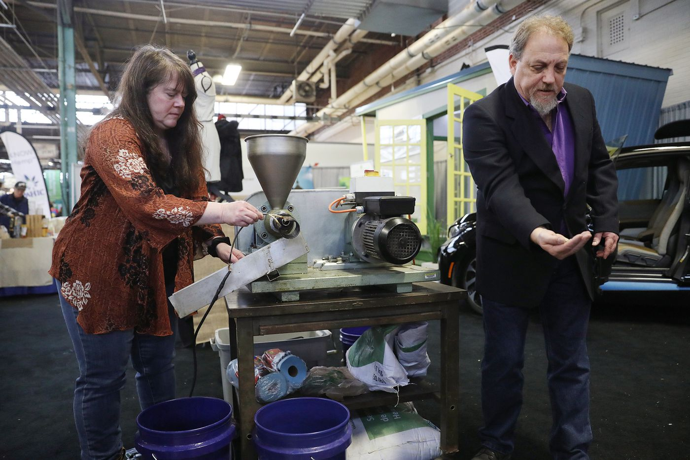 Erica Stark, left, executive director of the Pennsylvania Hemp Industry Council and the National Hemp Association, and hemp historian Les Stark demonstrate the hemp oil extraction process at the council's exhibit during the annual Pennsylvania Farm Show at the Pennsylvania Farm Show Complex & Expo Center in Harrisburg, Pa., on Tuesday, Jan. 7, 2020. The Hemp House stands behind them.