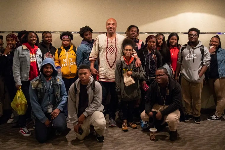 """Will Mega Ashantee, 47, dean of students at Charter High School for Architecture and Design, poses with CHAD  students after seeing the movie Harriet at the Ritz at the Bourse movie theater on Wednesday, Oct. 16, 2019. """"It's important for African American students and students in general,"""" Ashantee said. """"In order to move forward in the future, is to have a firm understanding of the past."""""""