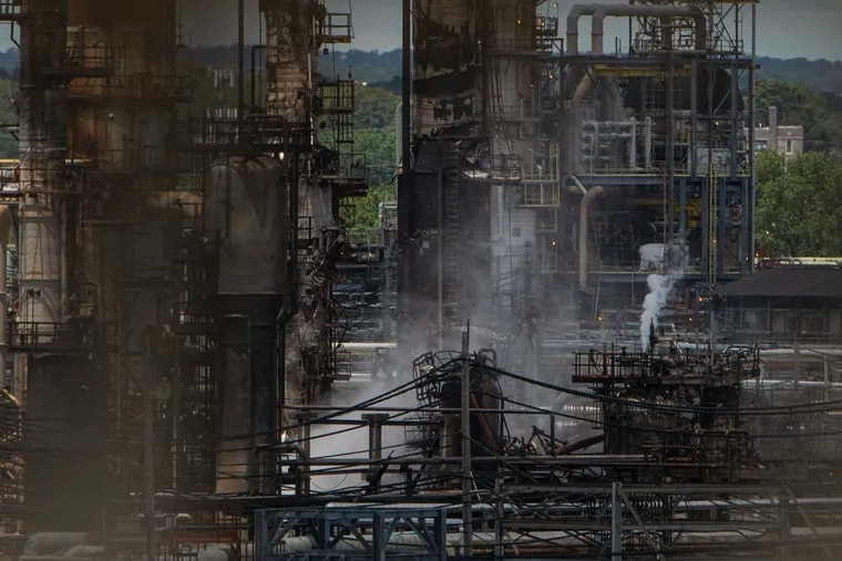 Damage is visible Saturday from the Platt Bridge as a fire smolders at the Philadelphia Energy Solutions refinery in South Philadelphia following Friday's explosion.