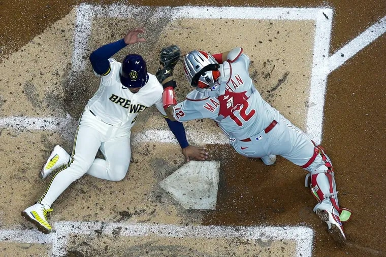 The Brewers' Eduardo Escobar scores safely past Phillies catcher Rafael Marchan during the third inning Tuesday in Milwaukee. Escobar scored from second on a hit by Christian Yelich.