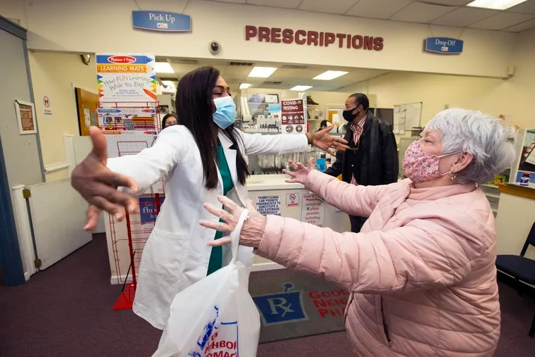 Pharmacist Chichi Ilonzo Momah (left) exchanges air hugs with customer SueMorelli. Her Springfield Pharmacy has pioneered providing vaccines to seniors and other vulnerable patients in the area. She is shown on March 4, 2021.