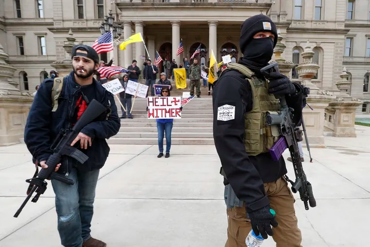 In this April 15 photo, protesters carry rifles near the steps of the Michigan State Capitol building in Lansing, Mich.