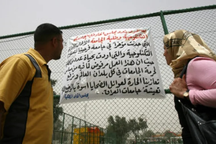 """Iraqi students read a banner expressing """"our warmest condolences"""" for the shooting victims of Virginia Tech yesterday at Baghdad Technology University. Universities and academics in the Iraqi capital have been among those hardest hit by the violence plaguing Iraq."""