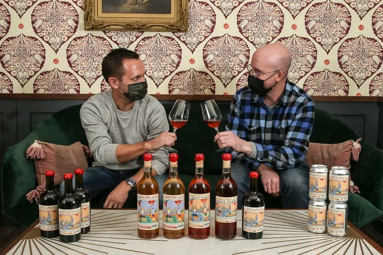 Bloomsday Owner Zach Morris, and Tim Kweeder toast with batch #5 on the tables ends and batches 1-5 center (l-r). Dumpster Juice Vermouth, a project from Bloomsday which has created 5 different batches of vermouth over the pandemic with seasonal, local ingredients.  Monday, January 11, 2021.