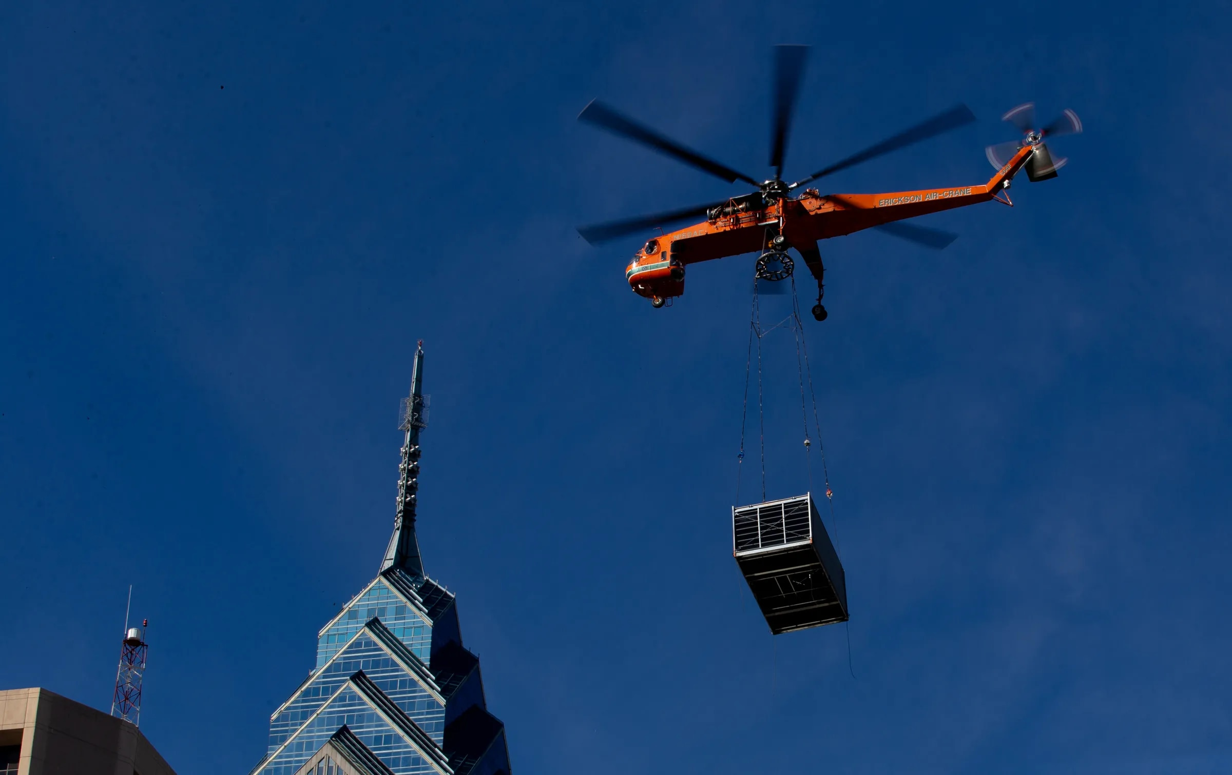 A helicopter flies over Center City while moving HVAC units to 2000 Market St. in 2019.