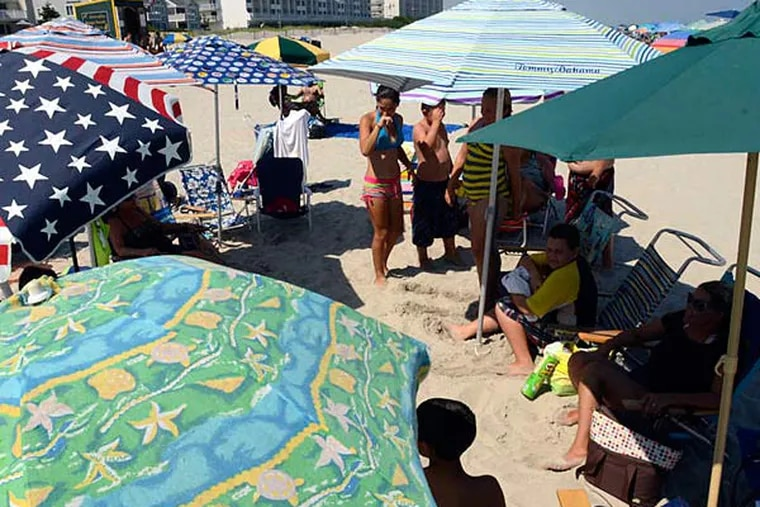 """The Carr, Bentz, Helms, Wilson, and Robinson mothers and children seek some shade in Sea Isle City. Sit out in the sun? """"We would look like leather,"""" Anne Marie Robinson said."""