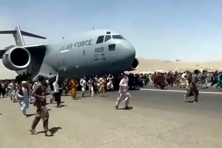 Hundreds of people run alongside a U.S. Air Force C-17 transport plane as it moves down a runway of the international airport, in Kabul, Afghanistan, on Monday.