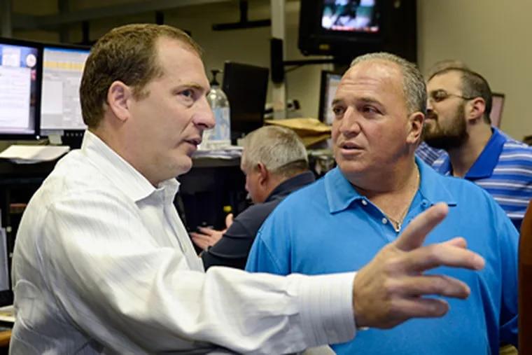 Tom Wittman (left), president of the Philadelphia Stock Exchange, talks with Nick DiCicco, owner of D&D Securities. (Tom Gralish / Staff Photographer)