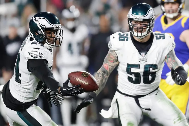 Eagles free safety Corey Graham (left) intercepts the ball as Chris Long looks on.