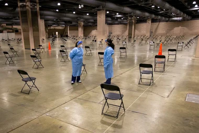 Nurses stand in the area where healthcare workers will take 15 minutes to rest and be observed after getting their COVID-19 vaccination at the COVID-19 vaccination site set up inside the Pennsylvania Convention Center on Friday morning January 8, 2021.