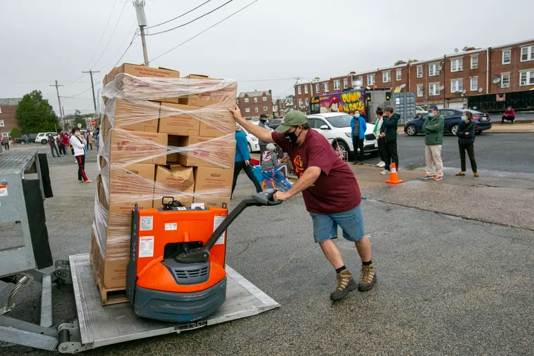 Employee of Share Food Program in Hunting Park drops off supplies to be given away. U.S. median household income declined while poverty increased in 2020.