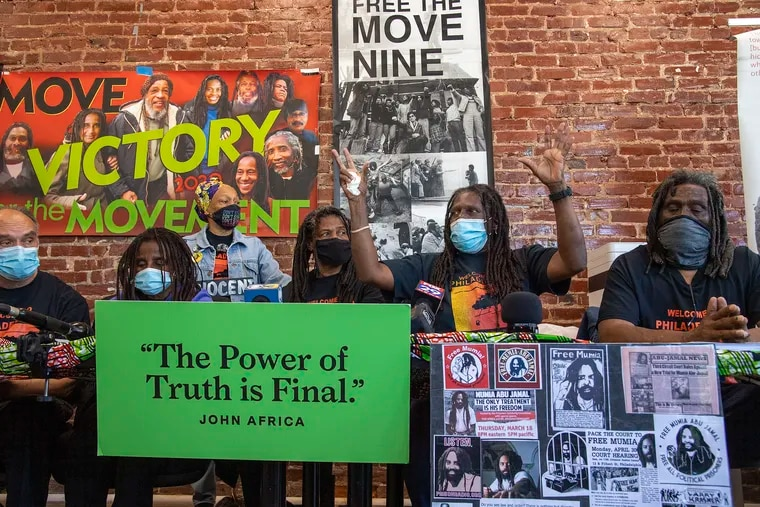 A family member of  MOVE, Consuewella Africa, raises her hands as she speaks during a press conference to denounce how two museums have handled the remains of a group member who died in the 1985 city bombing of their West Philly compound. Monday, April 26, 2021.
