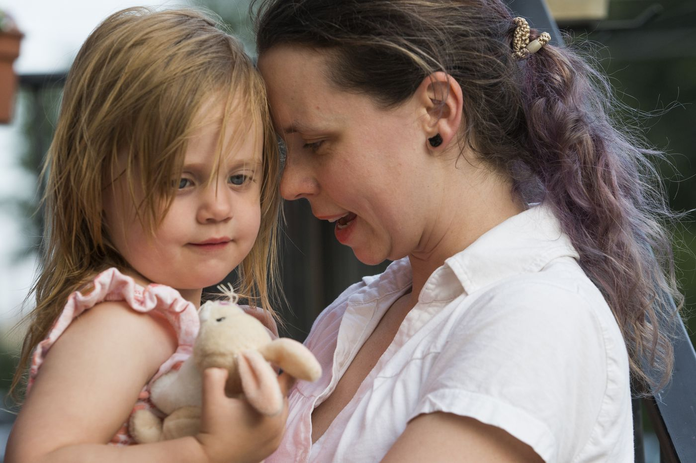 Rachel Kaminski holds her daughter, Emma, 2, outside their Fishtown home on June 30, 2017. Rachel and other residents have been reaching out to lawmakers about lead in the soil.