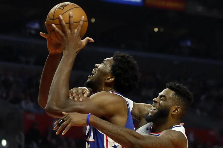 The Clippers' Willie Reed, right, fouls the 76ers' Joel Embiid on Monday night.