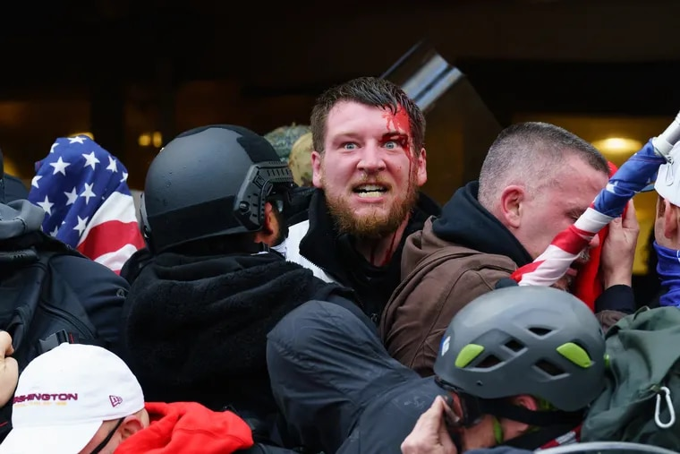 A rioter is bleeding after an injury sustained while trying to push past police through the doorway of the Capitol Building in Washington on Jan. 6.