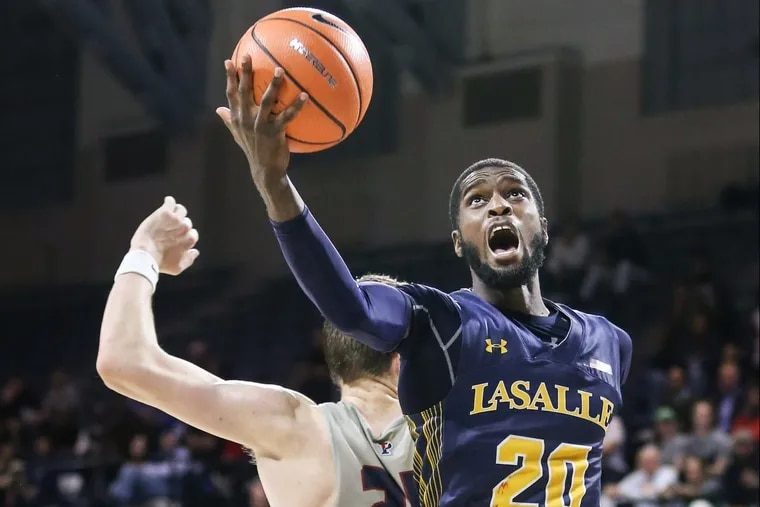 La Salle's B.J. Johnson grabs a loose ball over Penn's AJ Brodeur during the first overtime Monday night.