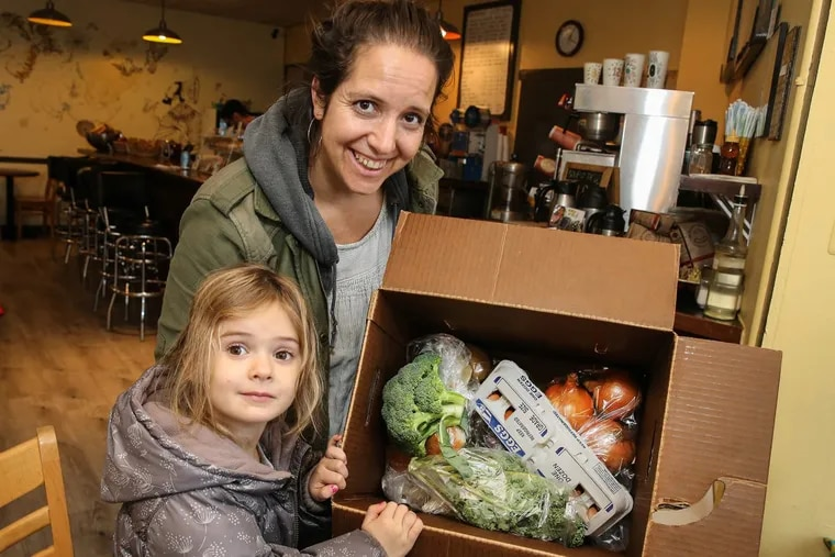 Rachel Swords and her daughter Milly, 4, with their box of local produce that they picked up at the B2 Coffee Shop on Passyunk Ave. Tuesday, November 21, 2017. STEVEN M. FALK / Staff Photographer