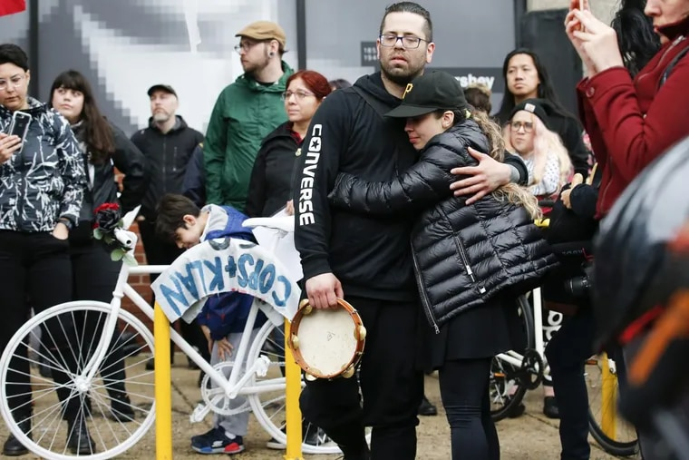 Bryan Avendano (center with tambourine), brother of killed bicyclist Pablo Avendano, is comforted during a Ghost Bike memorial at the corner of 10th and Spring Garden Streets. He was killed while working for a food delivery service.