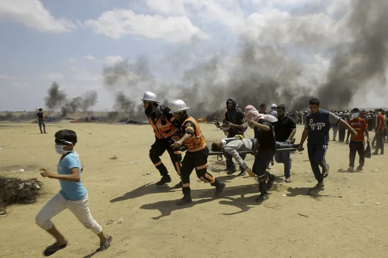 In this Monday, May 14, 2018 file photo, Palestinian medics and protesters evacuate a wounded youth during a protest at the Gaza Strip's border with Israel, east of Khan Younis, Gaza Strip.