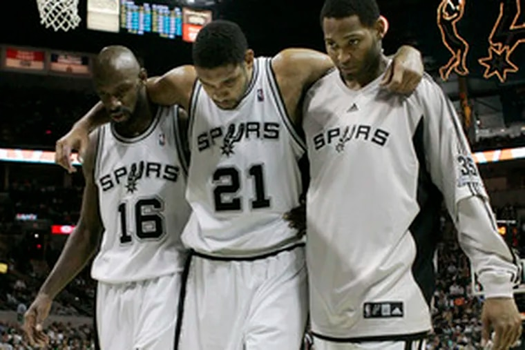 Tim Duncan is helped by Francisco Elson (left) and Robert Horry.