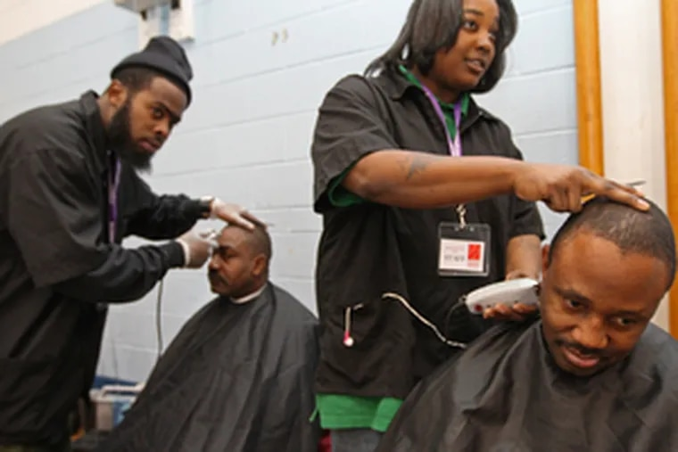 Levon Rutledge (right) gets his hair trimmed by Brittney Durosinmi of the Berean Institute. At left, Robert Rembert gets his hair trimmed by Saheem Lovelace of the institute.