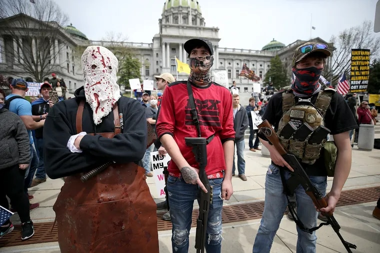 Protesters and militia gather outside the Capitol Complex in Harrisburg, Pa., on April 20, 2020. They are calling for Gov. Tom Wolf to reopen the state's economy during the coronavirus outbreak.