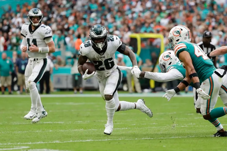 Eagles running back Miles Sanders runs with the football past Miami Dolphins defensive end Taco Charlton and defensive back Nik Needham on Dec. 1, 2019.
