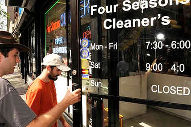 """At a dry cleaner on 19th Street , Jeff Deck holds the door for his partner, Benjamin Herson, as they seek to delete an unwarranted apostrophe (in """"cleaner's""""). With the permission of the owner, Deck used his fingernail to peel the apostrophe from the door. (Clem Murray / Staff Photographer)"""