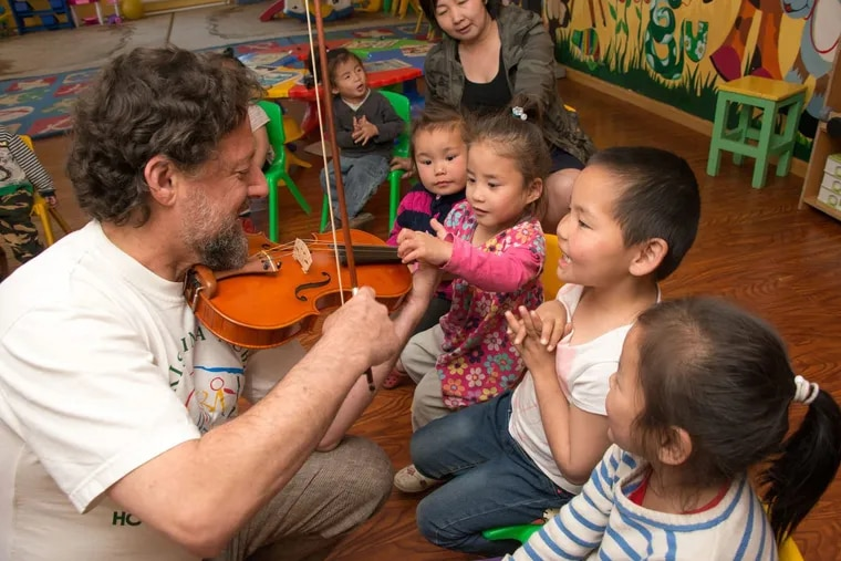 Philadelphia Orchestra musician Phil Kates plays for children at Blue Sky Orphanage in Ulaabaatar, Mongolia in June.