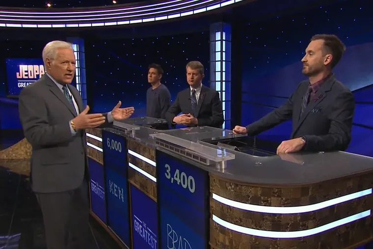 """Jeopardy! host Alex Trebek (left) speaks to contestants (from left) James Holzhauer, Ken Jennings, and Brad Rutter during the third night of the show's """"Greatest of All Time"""" tournament."""