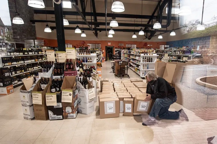 A Liquor Store employee prepares boxes for delivery at the Fine Wine & Good Spirits in Media. Stores are taking limited number of orders by phone from 9 a.m. to 1 p.m., or until the store reaches the maximum number of orders it can fulfill that day, starting Monday through Saturday.