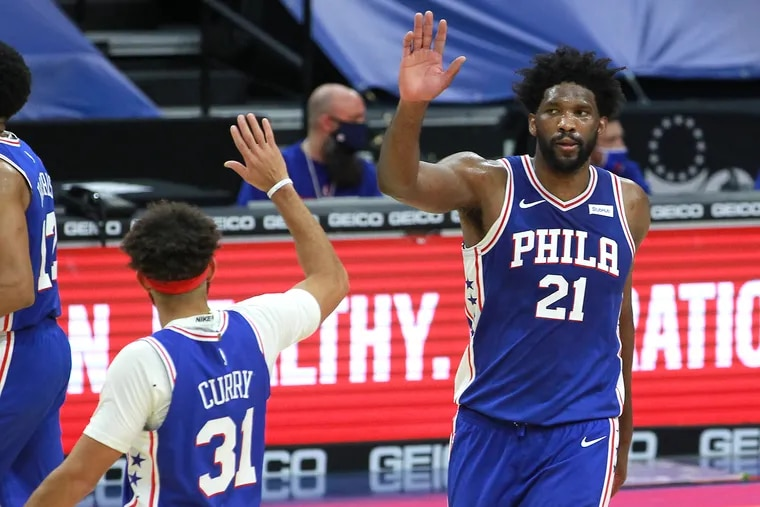Joel Embiid and Seth Curry celebrate late in the Sixers victory over the Raptors at the Wells Fargo Center on Tuesday.