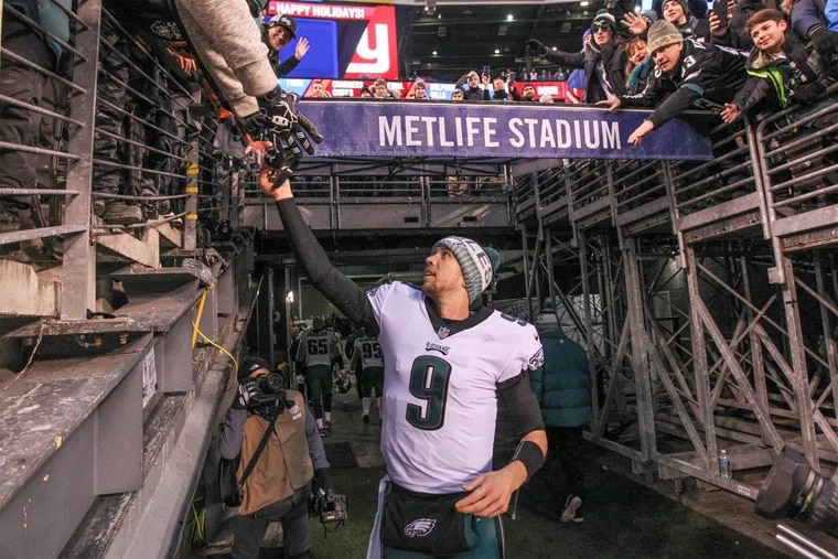 Eagle quaterback Nick Foles hands his gloves to a fan on the way to the lockerroom after the Ealges 34-29 win in New York. The Eagles versus the New York Giants at met Life Stadium on Sunday December 17, 2017. MICHAEL BRYANT/ Staff Photographer