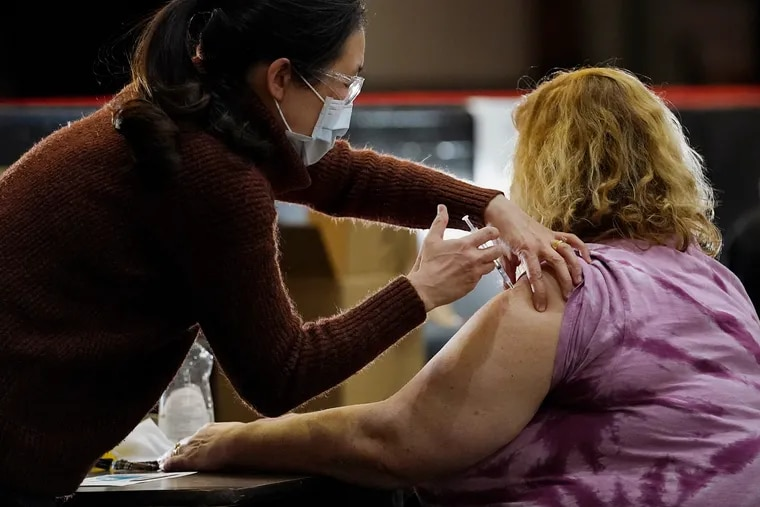 A health-care worker administers a COVID-19 vaccine at South Philadelphia High School in March.
