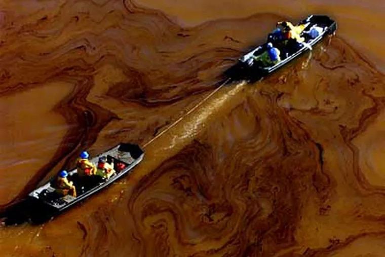 Boats carrying ecological workers pass through black oil swirled on the surface of the Delaware River after the Athos oil spill. (David Swanson / Staff File Photo)