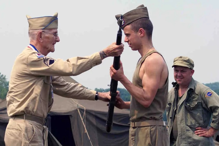 """Robert """"Red"""" Wells (left), a retired sergeant from the Army's 99th Infantry Battalion (Separate), instructs a young reenactor on proper weapon handling and drilling technique."""