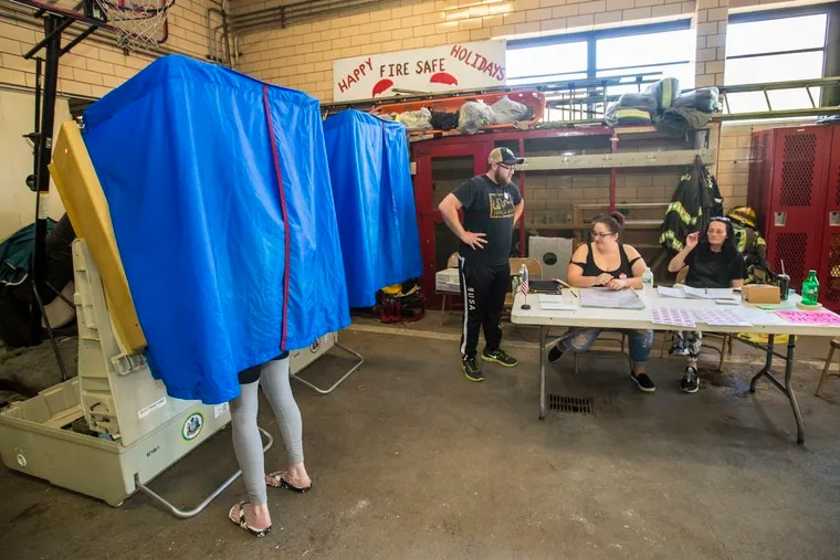 At the Engine 49 polling station John Chambers, inspector, left, Morgan Calvert, machine inspector, middle, and Dawn Chambers, clerk, right, work the tables in the back of the engine house in South Philadelphia as a voter cast their ballot on May 15, 2018.