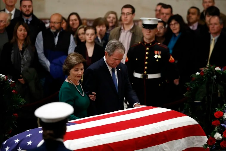 Former President George W. Bush and former first lady Laura Bush pause in front of the flag-draped casket of former President George H.W. Bush as he lies in state in the Capitol's Rotunda in Washington, Tuesday, Dec. 4, 2018. (AP Photo/Patrick Semansky)