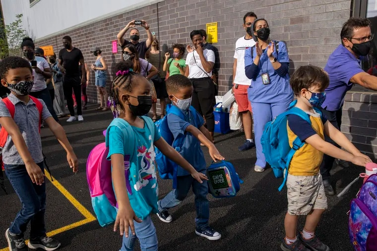 Students with arms out in front of them are attempting to keep socially distant from their classmates as they enter school on their first day of school last week.
