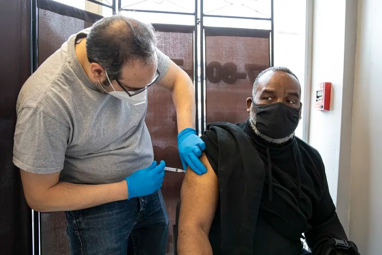 David Parker, of West Philadelphia, receive his first shot by pharmacist Ben Nachum, at Patriot Pharmacy on March 17.