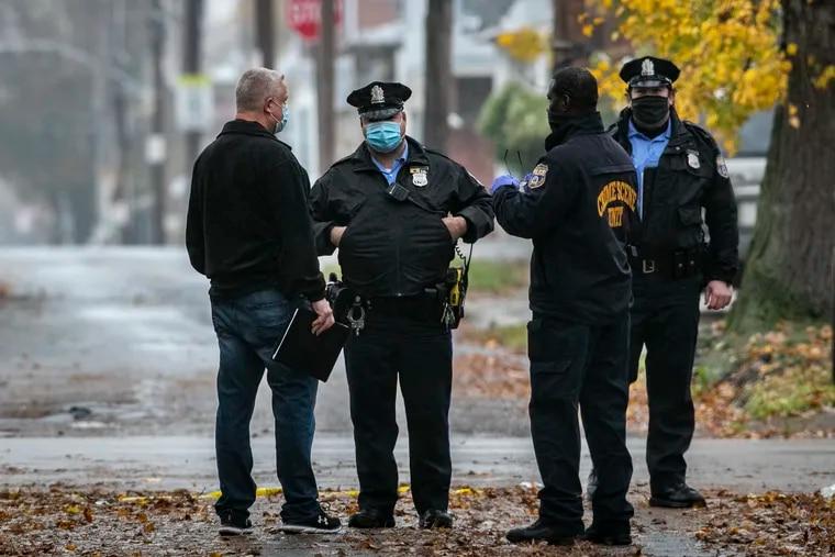 Masked Philadelphia Police investigate Edmund St. between Longshore and Disston St. on Friday, morning November 13, 2020.